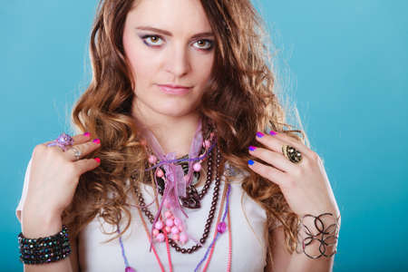 plentiful: Pretty young woman wearing bracelets rings and many plentiful of precious jewelry necklaces beads. Gorgeous fashion girl. Stock Photo