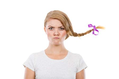 Expresión de la cara, los problemas de la adolescencia concepto. Adolescente en la toma de pelo rubio trenza viento caras enojadas.