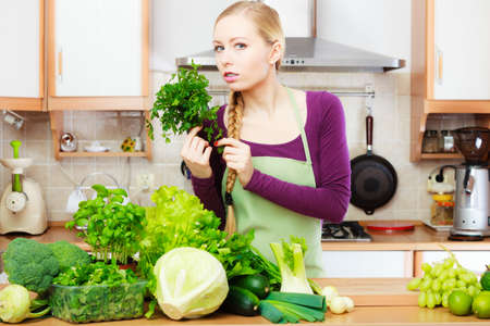 Woman in kitchen with many green leafy vegetables, fresh organically produce on counter. Young housewife holding parsley in hand. Healthy eating, cooking, vegetarian food, dieting and people concept. Stock Photo