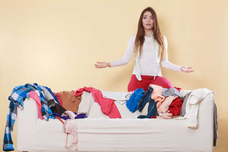 shrugging: Helpless woman standing behind on sofa couch in messy living room shrugging. Young girl surrounded by many stack of clothes. Disorder and mess at home. Stock Photo