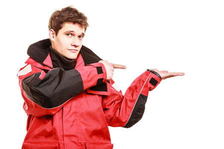Adventurous man making gesture showing open palm with space for product. Young male in weatherproof clothing. Adventure communication outdoors danger concept.
