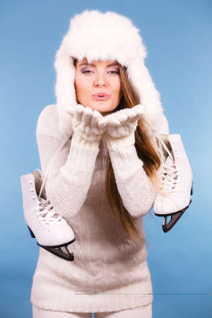 atractive: Winter sport activity concept. Atractive girl making kiss gesture wearing warm clothes, ice skates and furry hat, blue background studio shot.