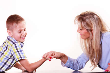 argue kid: Spending time with family fun and family bonds. Mother and son arm wrestle and have fun indoors.