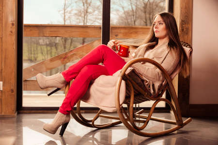 comfortable: Calm and coziness. Young woman at home sitting comfortable on rocker chair in front of window relaxing in her living room enjoying coffee or tea drink