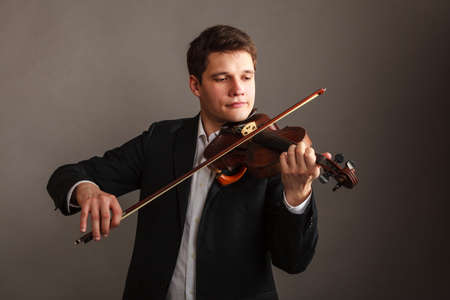 virtuoso: Music passion, hobby concept. Young man man dressed elegantly playing on wooden violin. Studio shot on dark background