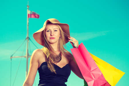 Spending money, buying things concept. Portrait of attractive elegant woman holding shopping bags wearing glamorous outfit with clear blue sky and polish flag in background