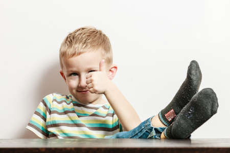 Free time, fun and expression. Little boy spend time indoors. Blonde child in striped shirt with legs on table and thumb up.