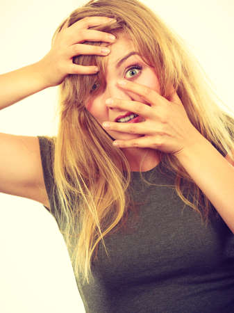 awkwardness: Emotions, embarrassment, awkwardness gestures concept. Ashamed blonde woman covering her face with hands. Studio shot on white background.
