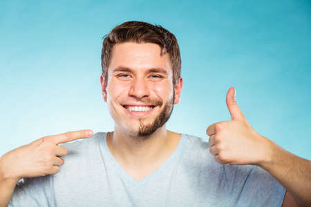 portrait of happy man with half shaved face beard hair smiling handsome guy on blue showing thumb up gesture skin care and hygiene 版權商用圖片
