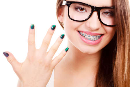 uñas pintadas: Vision and dentistry problems concept. Happy nerdy teenage wearing big eyeglasses showing her braces on teeth and painted nails.