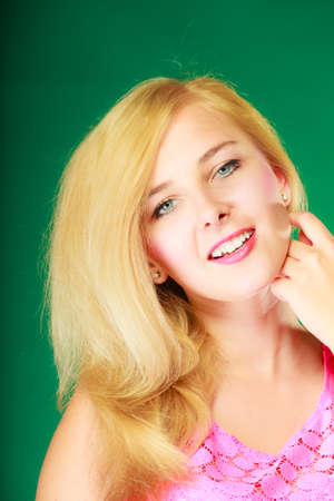 Dyeing, hairstyling, feminity, female beauty concept. Happy blonde woman in pink top. Studio shot on green background.