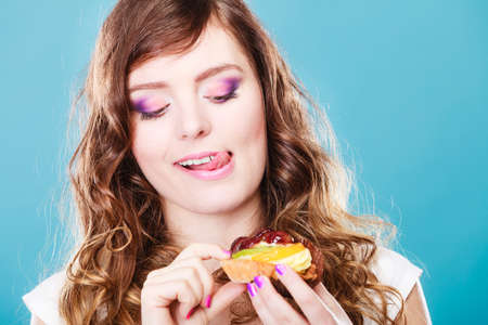 Süßer Speisezucker macht uns glücklich. Nette junge Frau bunte Make-up-Nägel hält Obstkuchen in der Hand blauen Hintergrund
