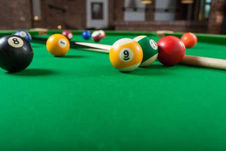 Boules de billard et queue de billard sur une table verte. jeu de billard