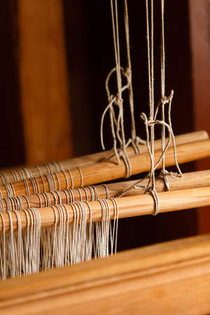 Traditional devices, vintage tailoring equipment concept. Oldfashioned thread on old spindle, spinning wheel Stock Photo