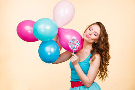 Woman attractive cheerful girl holding colorful balloons and sweet lollipop in hands. Summer holidays, celebration and happiness concept. Studio shot bright yellow background Stock Photo