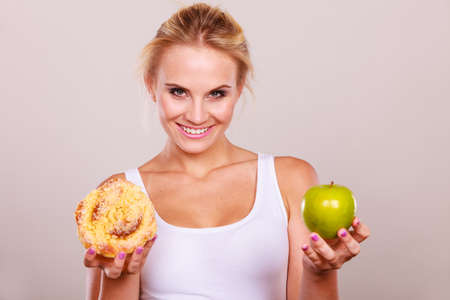 chose: Woman holds in hand cake sweet bun and apple fruit choosing, trying to resist temptation, make the right dietary choice. Weight loss diet dilemma concept. Stock Photo