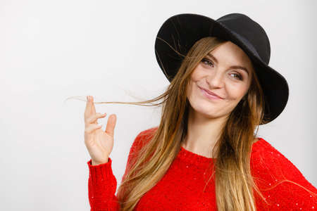 Fashion headwear clothing fun concept. Lady playing with hairs. Elegant girl wearing fashionable hat twisting her hair rolling it on finger.