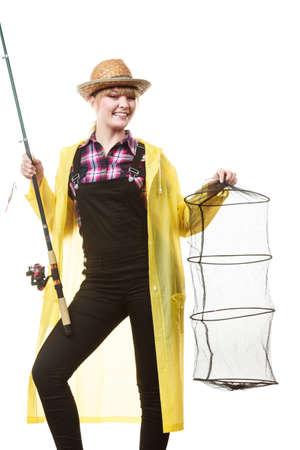 sportfishing: Spinning, angling, cheerful fisherwoman concept. Happy woman in yellow raincoat holding fishing rod and keepnet having fun. Stock Photo