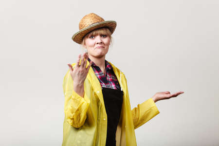 Suprised, shocked woman gardener in sun hat and yellow raincoat waiting for rain, gesturing with hands making funny face Stock Photo