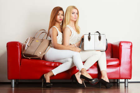 Fashion, clothes, clothing accessories, trendy outfits concept. Two women wearing light outfit and black high heels sitting on red sofa presenting bags