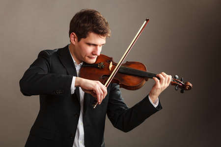 instrumentalist: Music passion, hobby concept. Young man man dressed elegantly playing on wooden violin. Studio shot on dark background