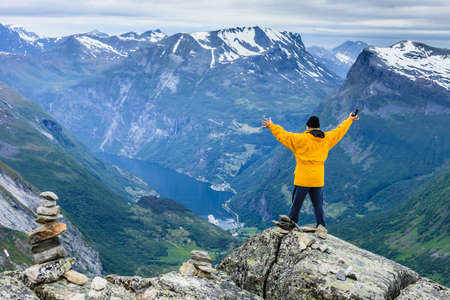Tourism vacation and travel. Happy free tourist man with arms raised outstretched up looking at Geirangerfjord and mountains landscape from Dalsnibba viewpoint, Norway Scandinavia.