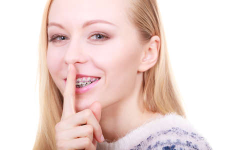 Gestures and signs concept. Young blonde woman making silence gesture with finger close to her mouth. Stock Photo