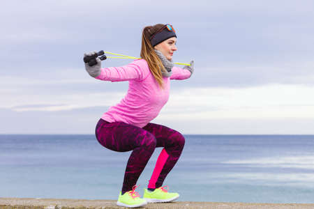 Woman athlete fit girl training outdoor with jumping skipping rope wearing warm sporty clothes in cold day. Sports activity in winter or autumn time, healthy lifestyle concept