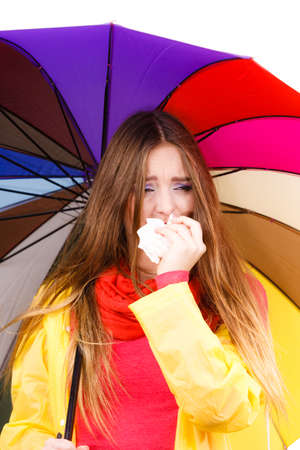 Woman rainy girl wearing rainproof yellow coat standing under colorful umbrella sneezing in tissue. Health care weather season concept. Stock Photo