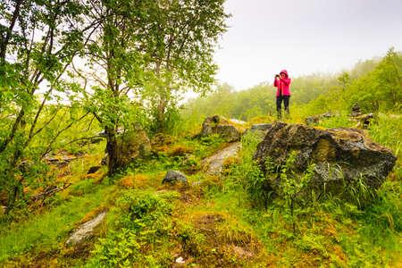 Toerisme vakantie en reizen. Vrouwelijke toerist fotograferen met camera in groene zomerbergen, wazige regenachtige dag, Noorwegen Scandinavië.
