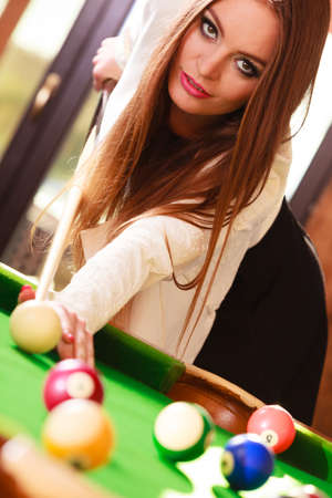 Competition concept. Young girl having fun with billiard. Beautiful fashionable woman playing spending time on entertainment.