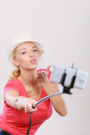 Technology, modern photography, confidence conept. Happy attractive adult blonde woman with sun hat taking picture of herself with smartphone on selfie stick. Stock Photo