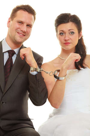 Couple problems, love forever concept. Bride and groom in handcuffs wearing wedding outfits Banco de Imagens