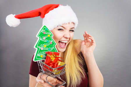 christmas spending: Seasonal shopping, sales during winter xmas time concept. Happy smiling woman holding shopping cart trolley with christmas tree and gifts