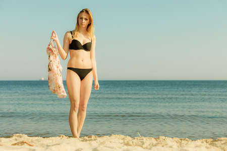 Relaxing during summertime, traveling, vacation concept. Woman in summer bikini walking on beach near sea, beautiful sunny weather. Stock Photo
