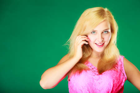 Dyeing, hairstyling, feminity, female beauty concept. Happy blonde woman in pink top holding hand close to her face. Studio shot on green background. Stock Photo