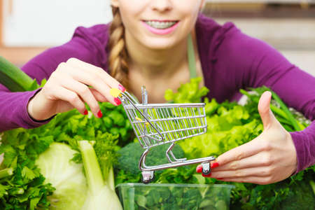 Buying healthy dieting food concept. Woman in kitchen having many green vegetables holding small shopping cart trolley. Stock Photo