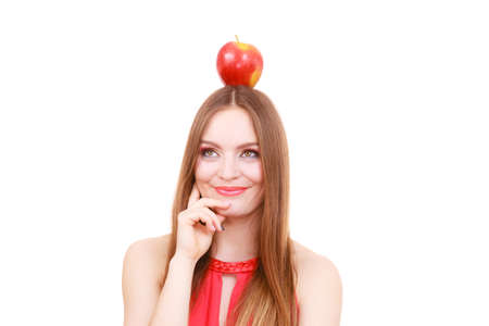 lose up: Woman young beautiful female long hair colorful make up holds big red apple fruit on head. Healthy eating, vegetarian food, diet and people concept