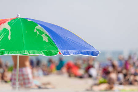 sunshade: Sunbathing equipment concept. Opened sun protective umbrella on sandy beach during summertime