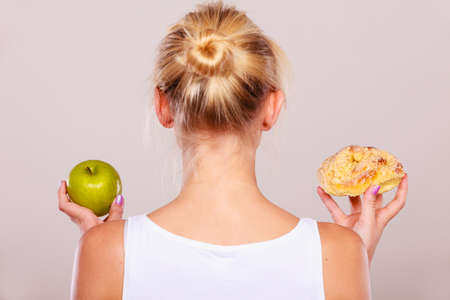 Woman back view holds in hand cake sweet bun and apple fruit choosing, trying to resist temptation, make the right dietary choice. Weight loss diet dilemma concept. Stock Photo