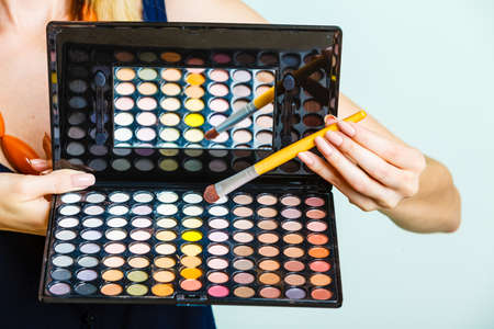 Cosmetic beauty procedures and makeover concept. Woman holds makeup professional eye shadows palette and brush. Make up applying. Stock Photo