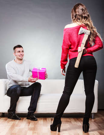 insincere: Guy giving present pink box to misleading girl. Insincere woman holding axe behind her back