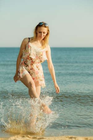 Summertime fun conept. Woman wearing short dress playing and having fun with water, enjoying summer vacation.