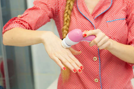 scrubbers: Deep cleaning face tools concept. Woman holding and presenting on hand facial cleansing brush machine.