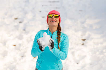 Young female holding snow. Relax fun in winter park. Health nature fashion fitness concept. Stock Photo