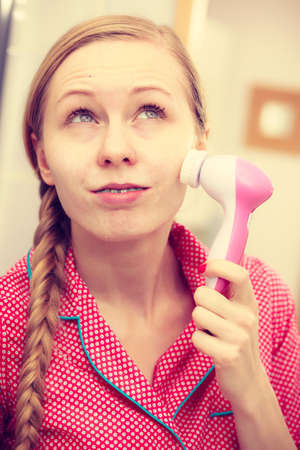 scrubbers: Deep cleaning face tools concept. Woman using facial cleansing brush  to clean her skin. Stock Photo