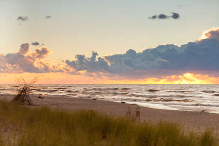 Amazing colorful sunset over evening sea horizon, clouds sky and sandy beach. Tranquil scene.