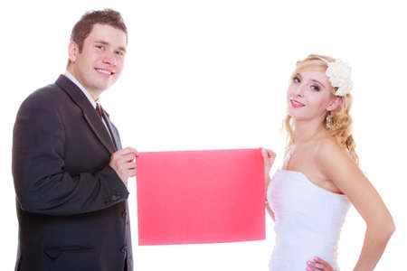 Positive relationship couples concept. Happy groom and bride posing for marriage photo waiting for the big day, holding blank red paper.