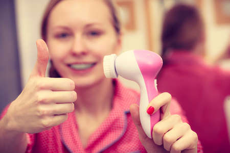 scrubbers: Deep cleaning face tools concept. Woman holding and presenting facial cleansing brush machine.