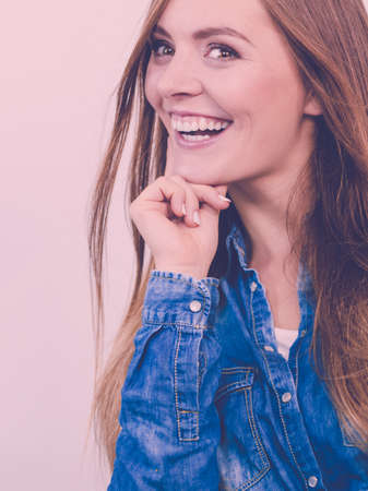 careless: Fashion, people, jeans concept. Beautiful girl is smiling. Young woman is wearing denim shirt. Stock Photo